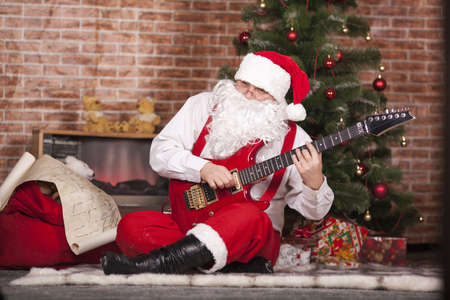 Santa Claus plays the guitar on the background of the Christmas tree and bag with gifts Stock Photo