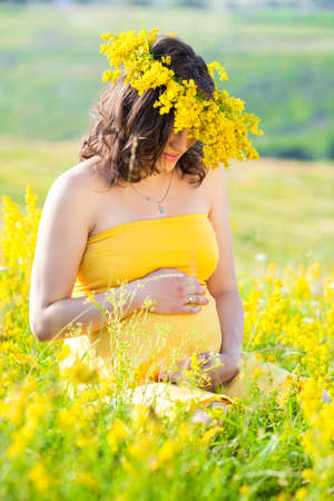 portrait of a beautiful pregnant woman with a wreath on head in the countryside Stock Photo