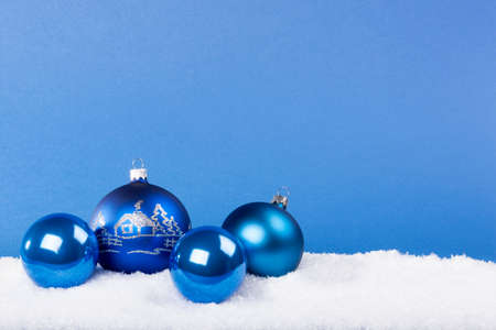 Blue Christmas balls in the snow with a blue background