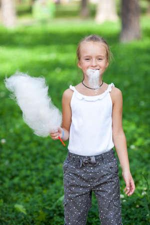 cotton candy: La muchacha linda con algod�n de az�car blanco en el parque de verano