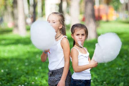 algodon de azucar: chicas lindas con algod�n de az�car blanco en el parque de verano