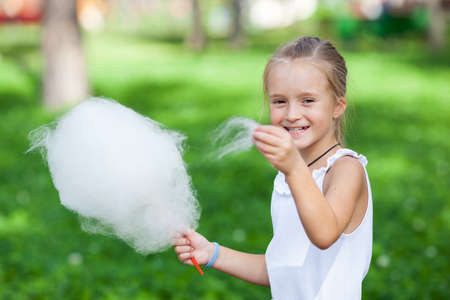 algodon de azucar: Cute girl with white cotton candy in the summer park