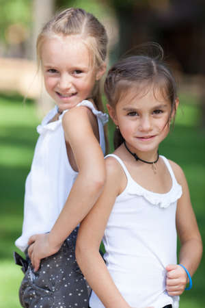 seven years: Wonderful happy girls standing on the lawn in the park. Girls seven years.