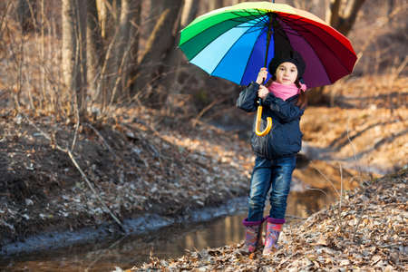 variegated: Girl with big multicolored umbrella in autumn park Stock Photo