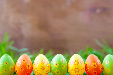 Easter eggs standing in a line in the grass on the background of wooden boards