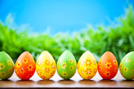 Easter eggs standing in a line in the grass against the blue sky Stock Photo