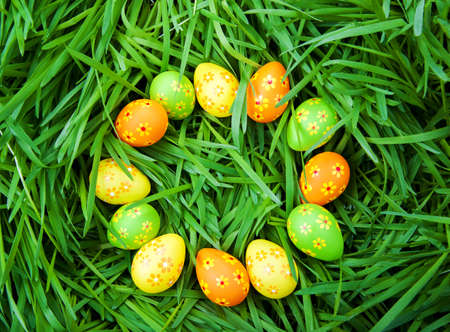 Multi-colored Easter eggs lie on the green grass Stock Photo