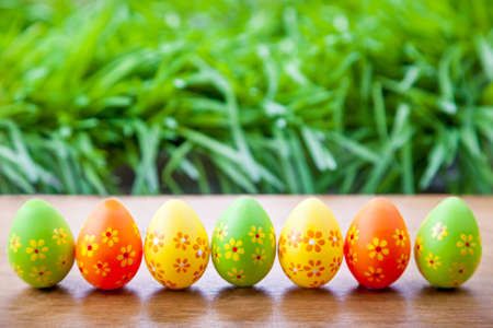 Easter eggs standing in a line in the grass