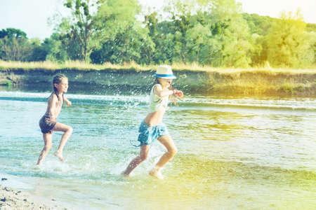 Happy children splashes water in a pond Stock Photo