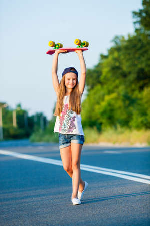A young girl with penny board outside the city at the road.