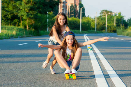 A young girls with penny board outside the city at the road.
