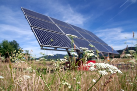 Solar panel with flower field and blue sky photo