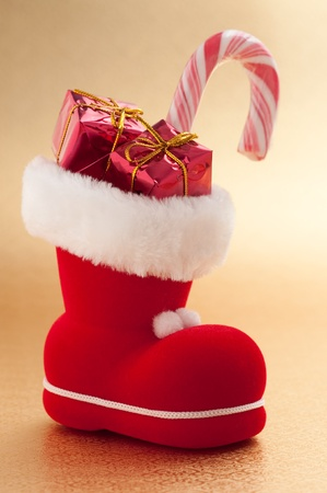 red christmas boot with gifts on gold background  photo