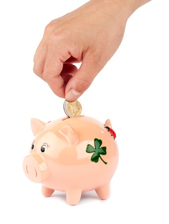 Woman putting coin in piggy bank isolated on white photo
