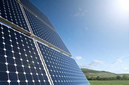 Solar Panel Against Blue Sky With Green Landscape photo