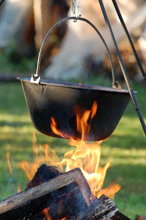 Typical Hungarian Gulyas  Soup  is jut cooking in Cauldron on Campfire photo