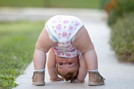 sweet baby girl: Un a�o de beb� ni�a jugando boca abajo en la calle