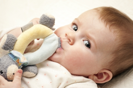 3 month: Baby Girl is looking at the camera with her toy