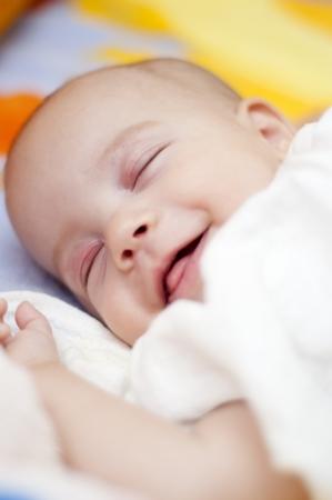 Dormire bambino sorride nel letto