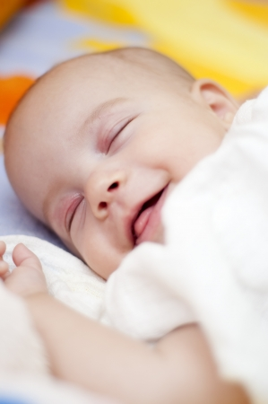 baby nursery: Sleeping Baby is smiling in the bed Stock Photo