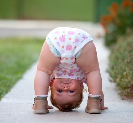 head down: One-year baby girl playing upside down on the street