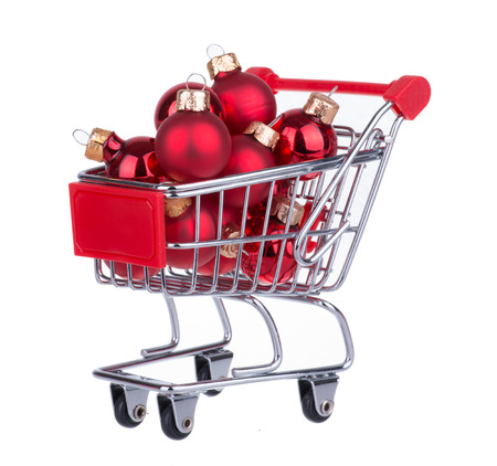 Shopping Cart With Red Christmas Balls For Decoration Isolated On White photo