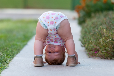 One-year baby girl playing upside down on the street photo