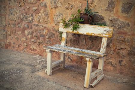 Empty Rustic wooden outdoor cottage bench painted white against wall photo