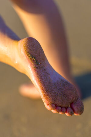 Sandy Female Feet On The Beach By Sunset photo