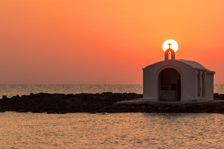 Catholic Church As Silhouette Against The Sunrise In Georgioupolis, Crete, Greece photo