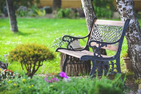 Pěkný lavice na zahradě v létě