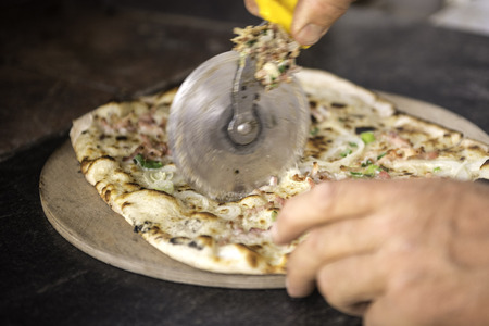 woodfired: Slicing Tarte Flambee, ATraditional French Dish. Fresh Baked In A Wood-Fired Traditional Adobe Oven. ( Flame Cake - English, Flammkuchen - German )