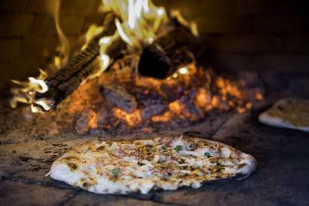 woodfired: Tarte Flambee, ATraditional French Dish. Fresh Baked In A Wood-Fired Traditional Adobe Oven. ( Flame Cake - English, Flammkuchen - German ) Stock Photo