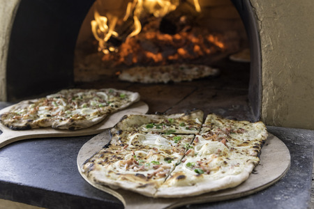 food and wine: Tarte Flambee, ATraditional French Dish. Fresh Baked In A Wood-Fired Traditional Adobe Oven. ( Flame Cake - English, Flammkuchen - German ) Stock Photo