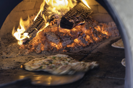 adobe: Tarte Flambee, ATraditional French Dish. Fresh Baked In A Wood-Fired Traditional Adobe Oven. ( Flame Cake - English, Flammkuchen - German ) Stock Photo