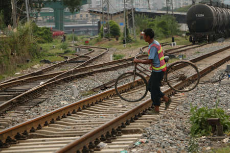 persistent: A man carrying a bicycle across the railroad Editorial