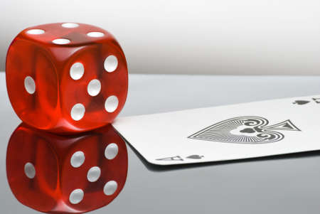 Red dice with reflection and playing card Stock Photo