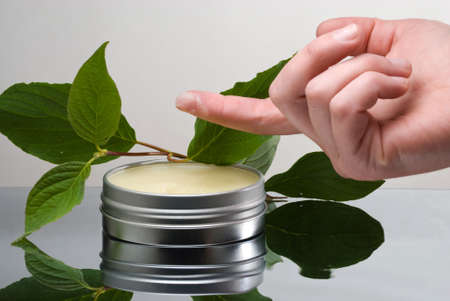 Container with salve near fresh plant and dab of salve on tip of female finger