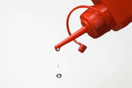 emulsifier: Dripping plastic oil can over white