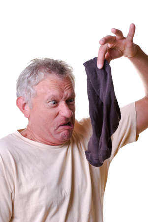 Expressive man is keeping stink sock Stock Photo