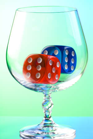 Red and blue dices in transparent snifter