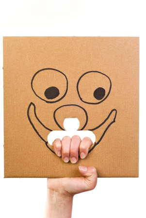 Sheet of corrugated cardboard with sketch of smiling face in hand isolated on white Stock Photo