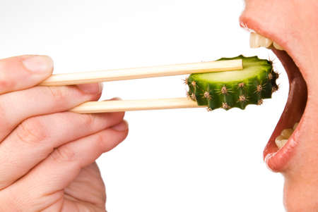 Slice of cactus in chopsticks is placed in the mouth Stock Photo
