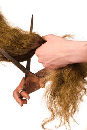 Scissors cutting long beautiful hairs on white background