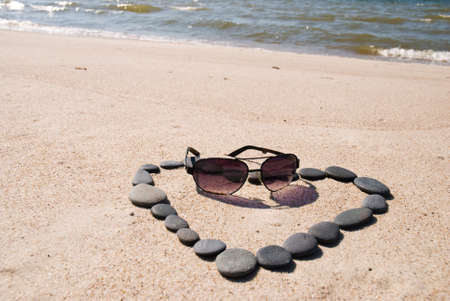 Heart made from stones and sunglasses on the beach Stock Photo