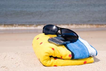 Towel, mobile phone and sunglasse on the seashore