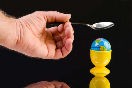 Globe sitting in an eggcup about to be smashed by a spoon photo