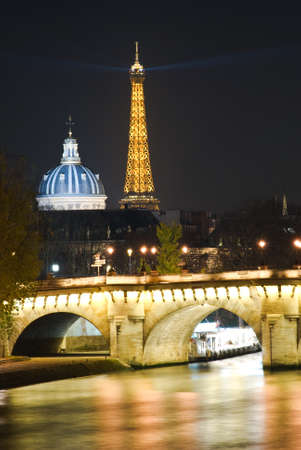 Eiffel Tower and Dome of the Institut de France at night, view from Seine river