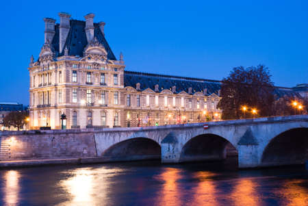View of the Louvre Museum at dusk, across the Seine River, Paris, France Editorial