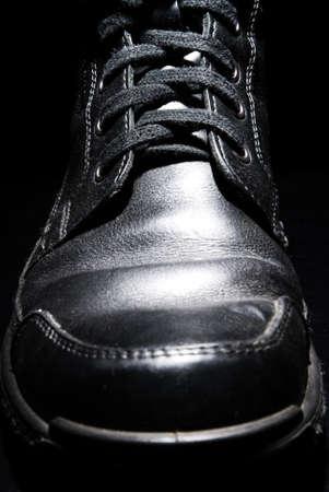 Close up of shiny men shoe on black background